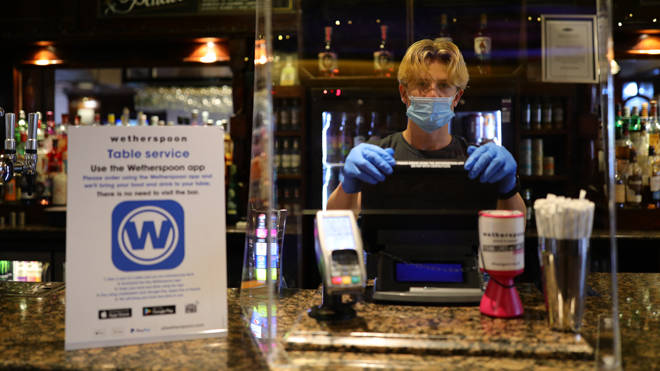 A member of staff in PPE waits to serve drinkers at the reopening The Toll Gate, a Wetherspoons pub in Hornsey, north London
