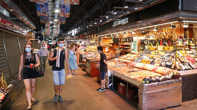 Shoppers in a market in Spain during the coronavirus crisis - file image