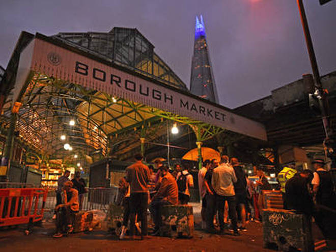 The Shard is lit blue in honour of the NHS as people are out in Borough Market, London