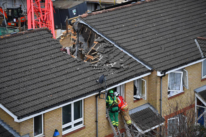 A woman has died after a crane collapsed onto some homes in Bow, east London