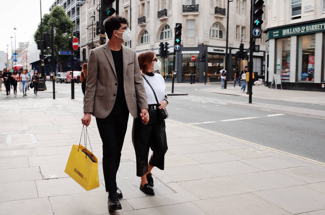 Shoppers carry a bag of shopping from department store Selfridges along Oxford Street
