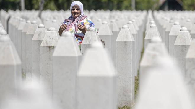 A woman prays at the memorial cemetery in Potocari, near Srebrenica, Bosnia