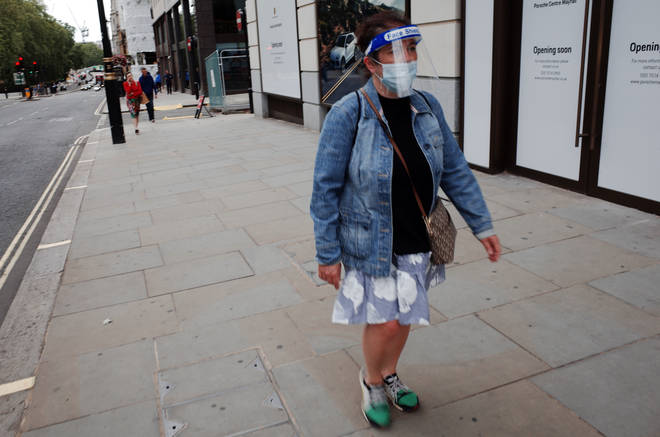 A woman wearing a face mask and face shield walks along Piccadilly in London