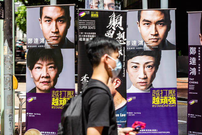 A man wearing a face masks walks past posters of pan-democratic candidates