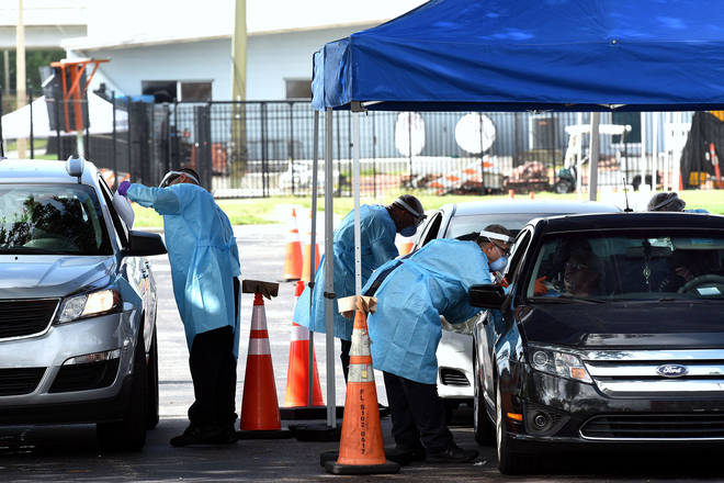 People are tested for COVID-19 at a drive through testing site in Orlando