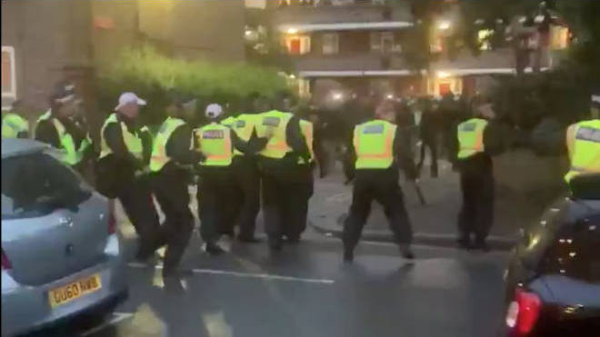 Police appeared to be pelted with bottles while dispersing a party in west London