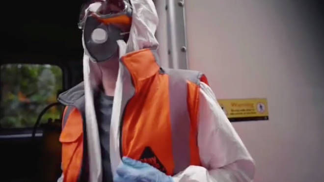 The artist is shown wearing PPE and a mask