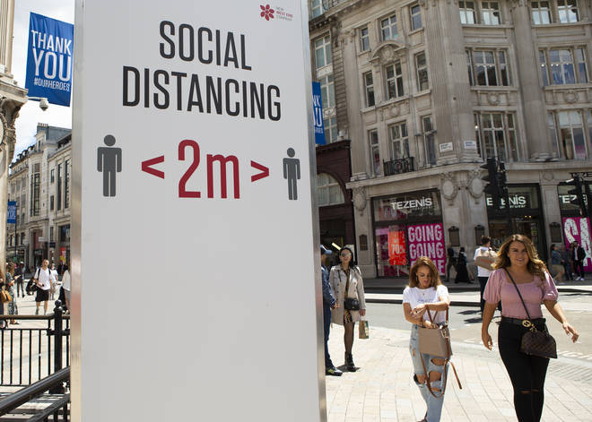 Shoppers walk past a social distancing sign in London
