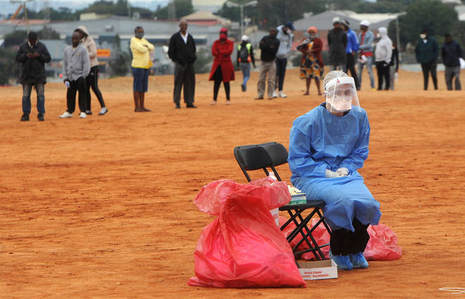 A medical practitioner waits for patients to test for COVID-19 in Alexandra township, Johannesburg