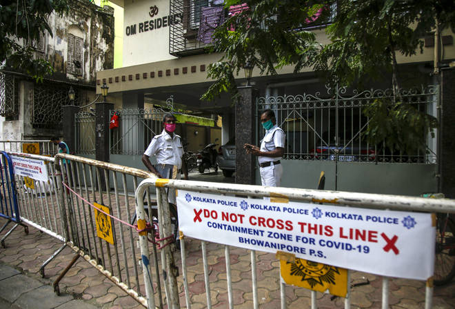 Policemen stand guard outside a residential complex where some residents tested COVID-19 positive in Kolkata, India
