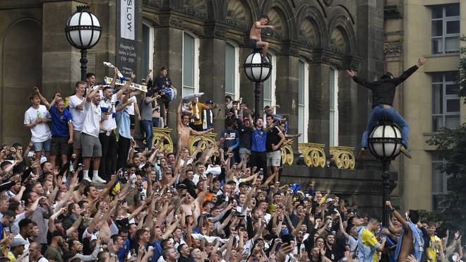 Leeds United fans celebrate after winning the Sky Bet Championship title at Millennium Square
