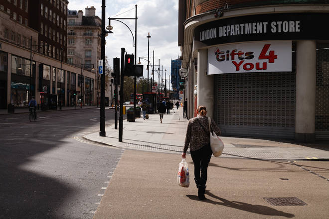 A woman carries a bag of food shopping past shuttered stores on a near-deserted Oxford Street