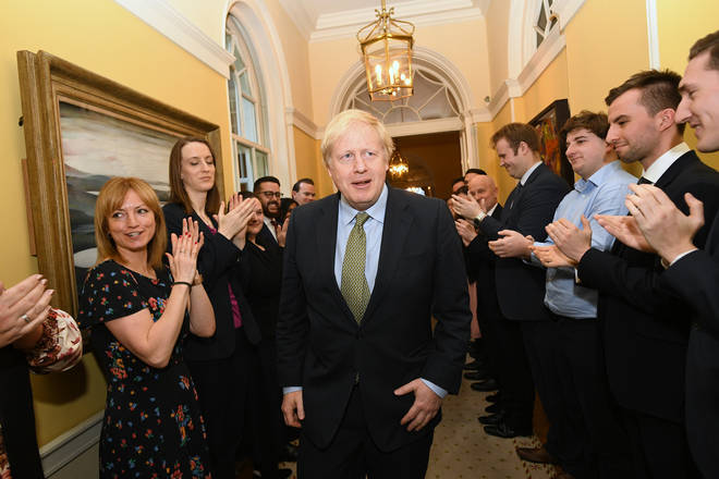 Prime Minister Boris Johnson is greeted by staff as he arrives back at 10 Downing Street in December