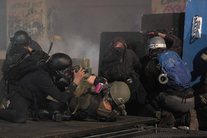 Press photographers take cover as officers fire tear gas at protesters