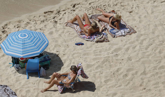 Three women relax on the beach in Spain