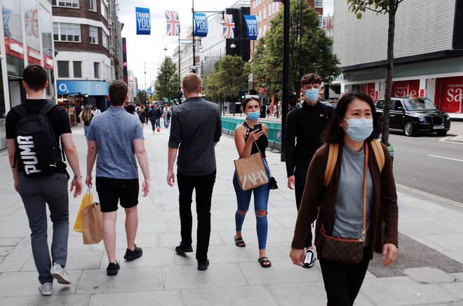 File photo: Shoppers wearing face masks walk along Oxford Street in London