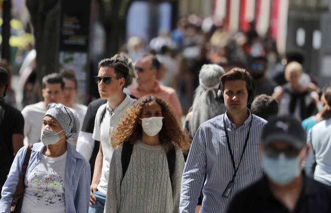 File photo: Shoppers wearing face masks walk along Oxford Street in London