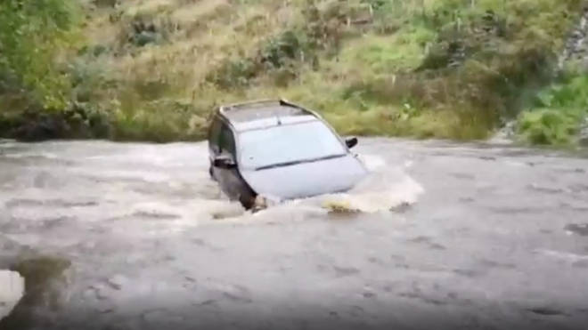 A car was swept away in a river in Carmarthenshire after heavy rain across Wales