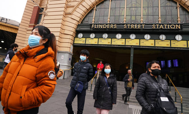 People wearing face masks outside Melbourne's iconic Flinders Street Station
