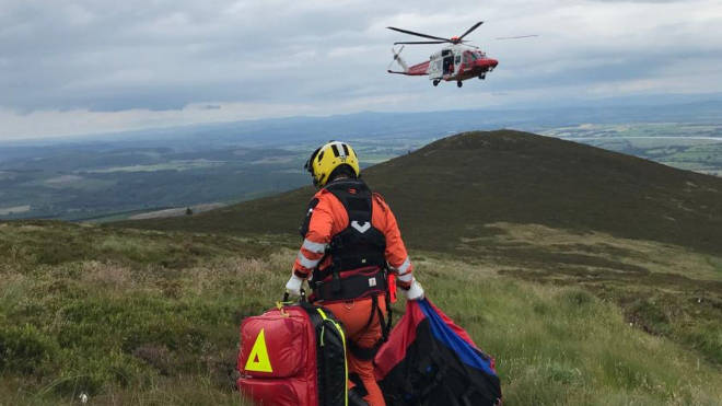 A Search and Rescue helicopter assisting a walker near Dumfries, Scotland