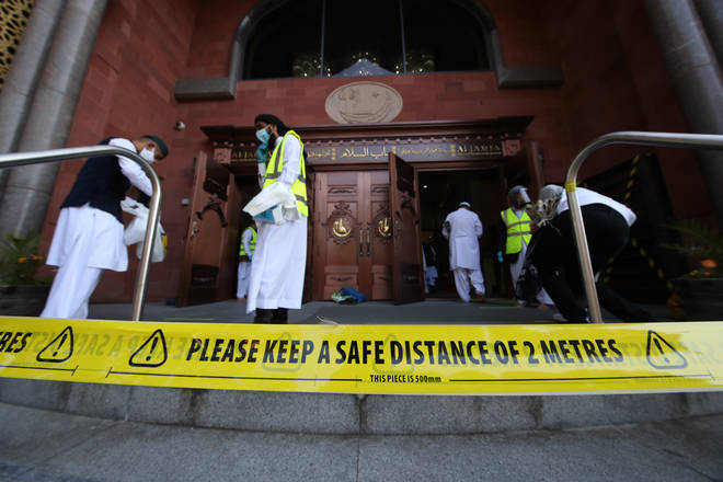 Worshippers observe social distancing as they arrive at the Bradford Grand Mosque in Bradford, West Yorkshire, on the first day of Eid, one of the areas where new measures have been implemented to prevent the spread of coronavirus.