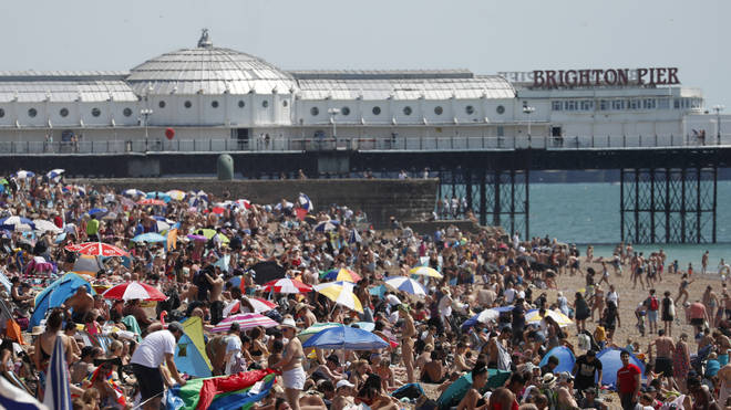 Beachgoers in Brighton enjoy the sunshine on what is now Britain's hottest day of the year so far