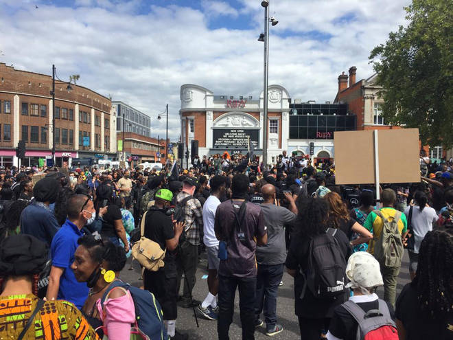 Hundreds have turned up to a protest in Brixton as police impose a curfew