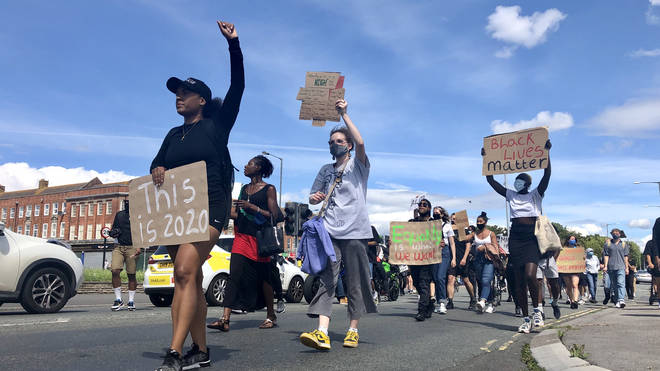 People marched down the road in protest against a hit-and-run which police say was racially aggravated