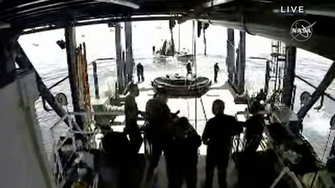 Crew wait for the recovery of Crew Dragon after its landing