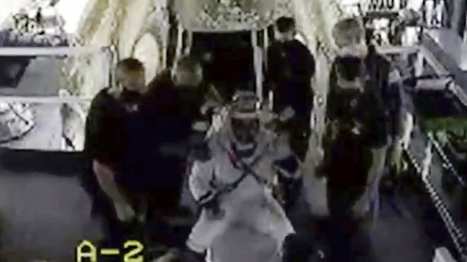 Doug Hurley waves as he is assisted out of the SpaceX capsule