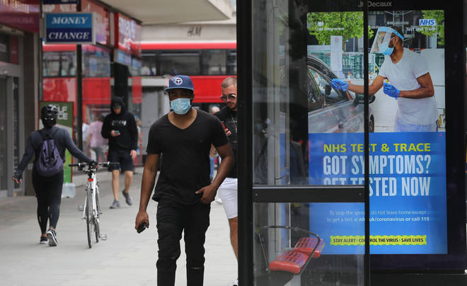 A pedestrian walks past a screen on a bus stop displaying a NHS notice on test and trace on Oxford Street