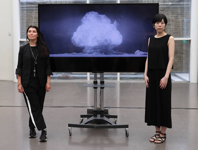 Artists Es Devlin and Machiko Weston pose next to their digital art collaboration 'The End of the World' at Imperial War Museum London