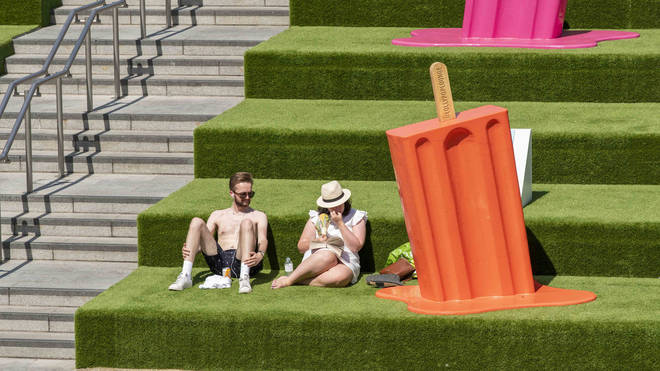 People seen enjoying the sun in Coal Drops Yard next to a giant ice lolly as temperatures soar