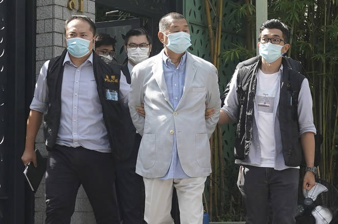 Hong Kong media tycoon Jimmy Lai, center, who founded local newspaper Apple Daily, is arrested by police officers at his home in Hong Kong