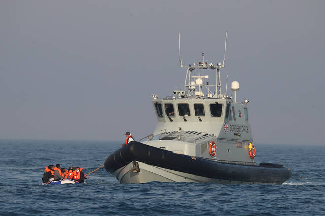 Border Force officers assist a group of people, thought to be migrants, aboard HMC Hunter after they were stopped as they crossed The Channel in a small boat headed in the direction of England