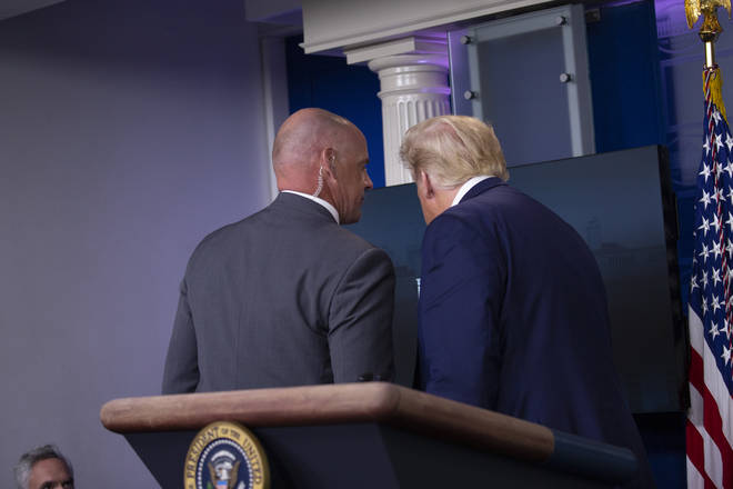 United States President Donald J. Trump is removed from the White House Briefing Room by a US Secret Service agent