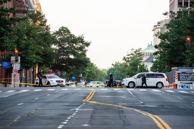 Police officers secure the streets around the locked White House after shots were fired