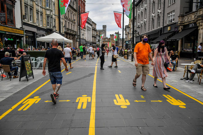 Yellow markings along the pedestrianised area of Cardiff city centre direct people to aid social distancing