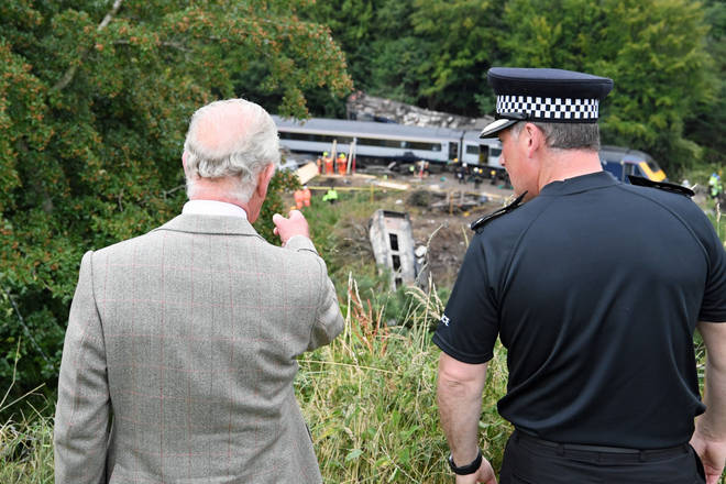 Prince Charles inspects the site of the train crash as he met with emergency workers
