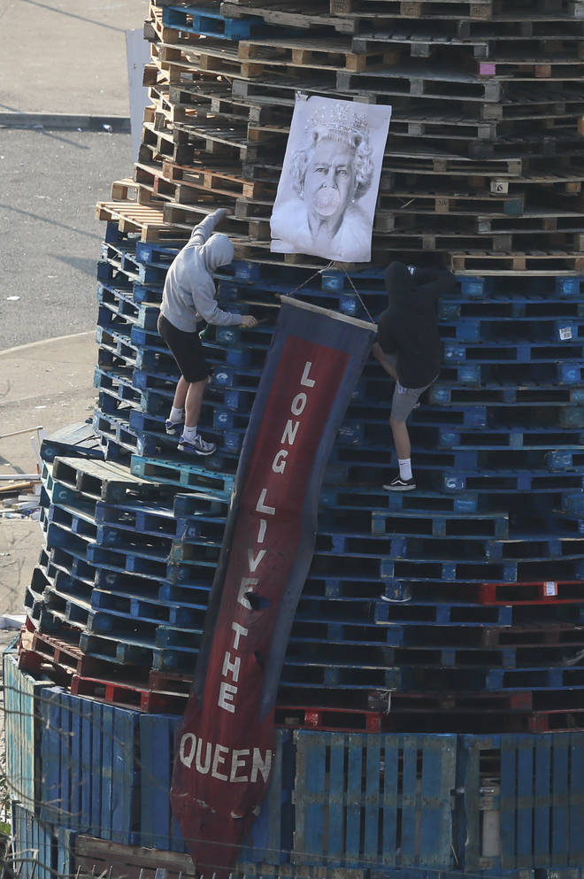 An image of Queen Elizabeth II is added to a bonfire in the Bogside area of Derry City