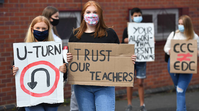 Students hold placards calling for a u-turn over their A-level results