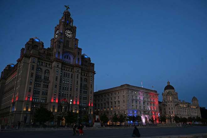 The Royal Liver Building (L) lit up by red, white and blue lights to commemorate the 75th anniversary of VE Day