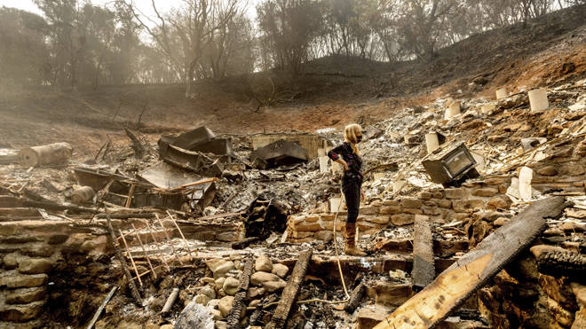 A woman surveys the remains of her partner's property in California