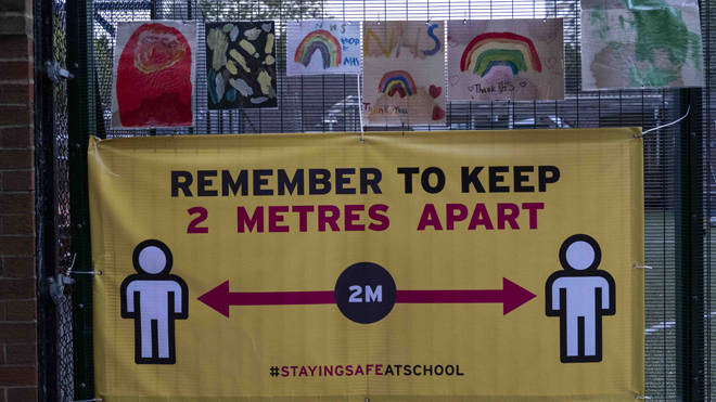 A social distancing banner on school gates
