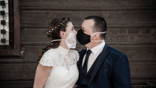 Newlyweds Silvia and Petar are seen kissing with protective masks in front Varna Wedding Ritual Home. Wedding during covid-19