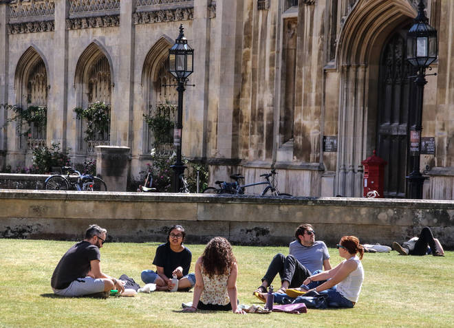 File photo: People sit on the grass outside the main entrance to Kings College, part of Cambridge University