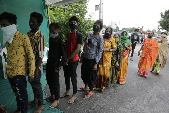 People stand in a queue to test for COVID-19 at a check post erected to screen people coming from outside the city, in Ahmedabad, India