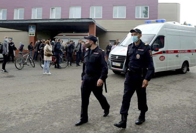 Police officers walk outside Omsk Ambulance Hospital No 1