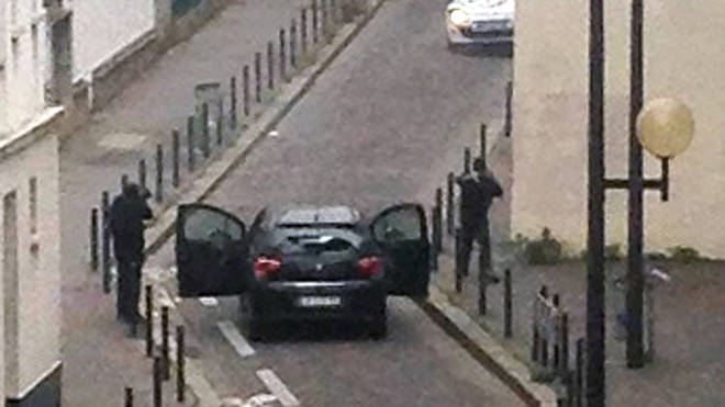Armed gunmen face police officers near the offices of the French satirical newspaper Charlie Hebdo in Paris on January 7, 2015