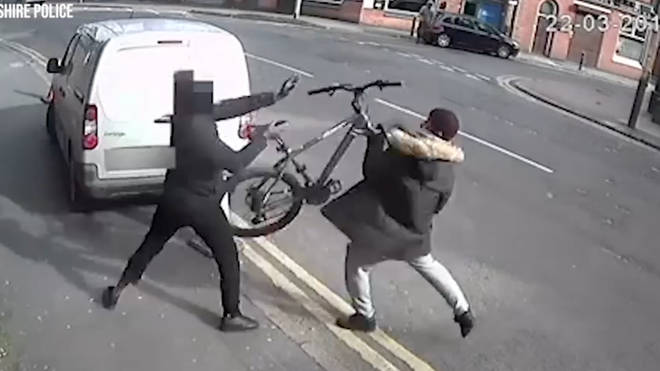 The cyclist throws his bike at the attacker in an attempt to escape
